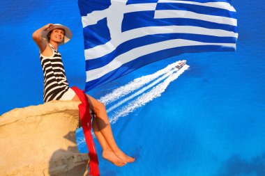 Sexy woman on the rock above azure sea with Greece flag
