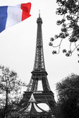 Famous Eiffel Tower with colorful flag in Paris, France