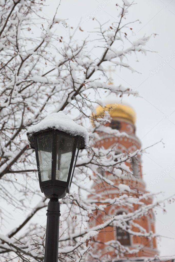 Bell tower and streetlight. Orthodox monastery Davidova Pustin in winter. Chekhov. Moscow region. Russia.