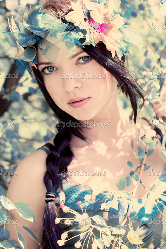 Young beautiful girl among the flowering trees