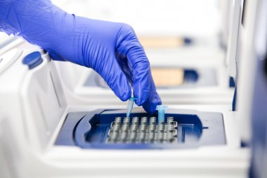 Scientist with DNA copying, Real-time cycler close
