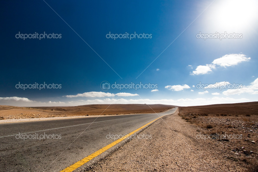 Empty desert road with blue sky.