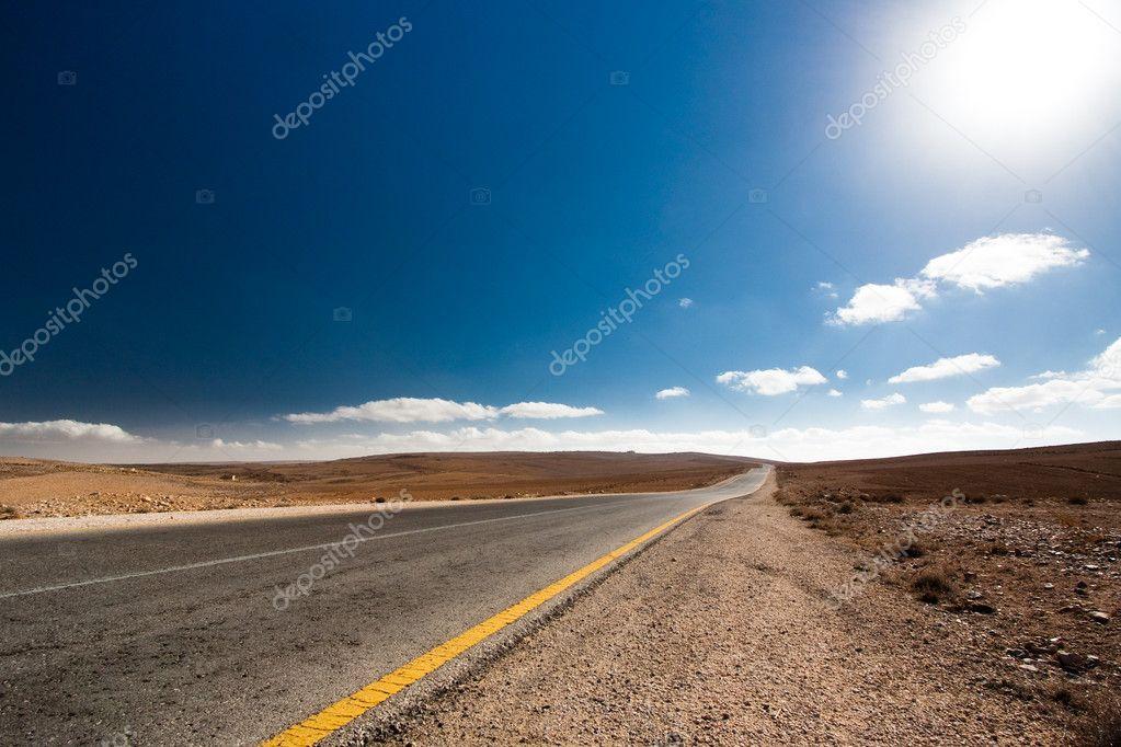 Empty desert road with blue sky.