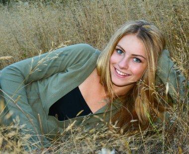 Beautiful teenage girl laying in tall grass