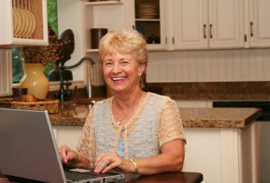 Grand-ma in the kitchen using her laptop