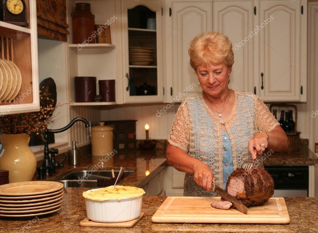 abuela en la cocina del país tallando un asado de carne de res ...