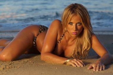 Beautiful bikini girl on beach at sunset