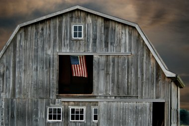 Old barn at sunset with flag