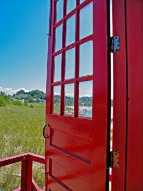Red door opened to beach scene