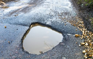 Deep, waterfilled pothole in the road