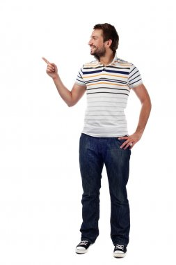 Young casual man pointing. Isolated