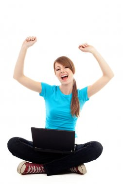 Female student with raised arms sitting with laptop