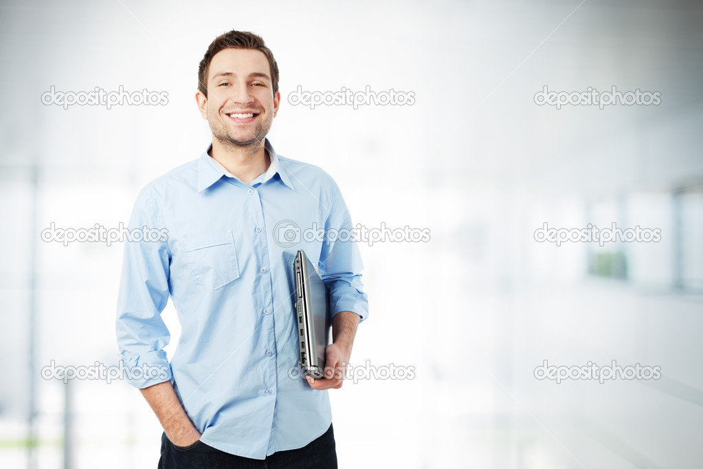 Happy businessman with laptop smiling