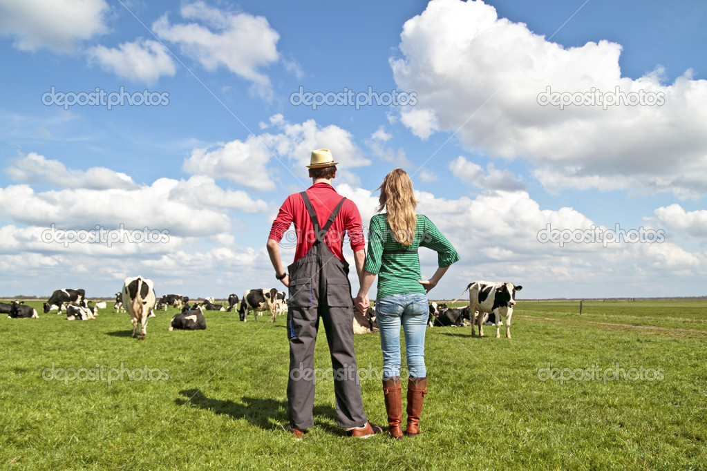 The farmer and his wife proudly looking at their cows