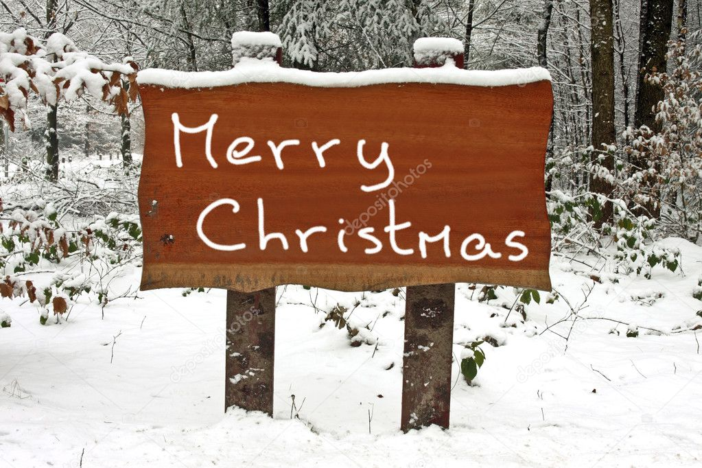 Merry Christmas written on a snowy wooden sign in winter
