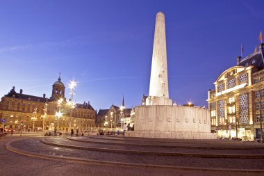 The National Monument on the Dam and in the background the Royal Palace in Amsterdam the Netherlands at twilight