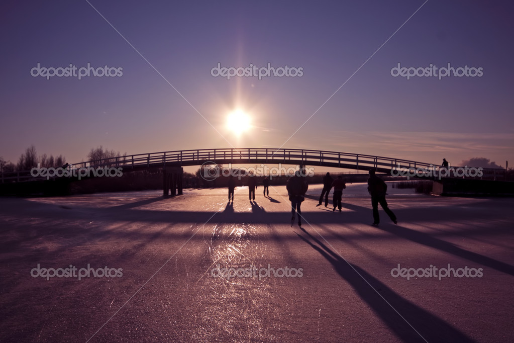 Ice skating at sunset on the canals in the countryside of the Netherlands