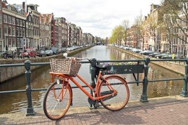 Orange bike on the bridge in Amsterdam city in the Netherlands