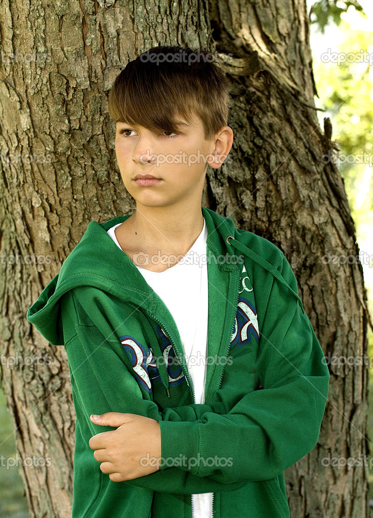 young teen boy by tree stock photo trudywilkerson