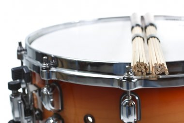 Unplugged drumsticks resting on a snare drum