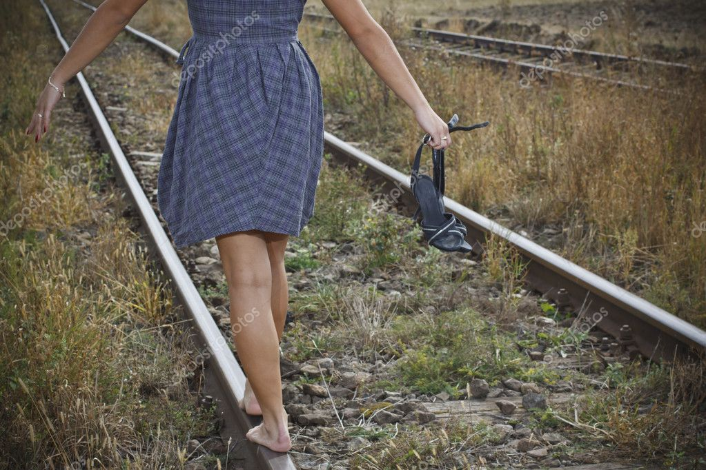 Young woman with shoes in her hand on the railway — Stock ...