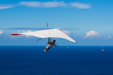Hang Gliding over a deep blue Ocean on a clear day