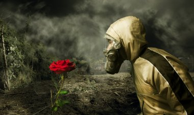 Man in a gas mask with a rose