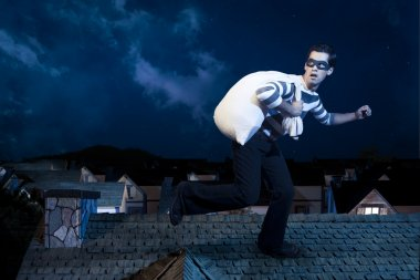 Thief on the roof running away at night