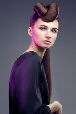 Beautiful woman with a luxurious and healthy hair on natural background. Professional makeup and hairstyle