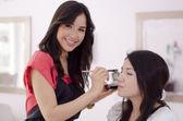 ženské maskérka použití make-up na klientovi