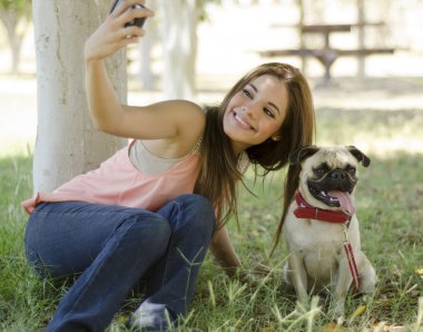Young beautiful woman taking a picture with her dog at the park