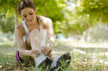 Cute young woman tying her shoelaces before running