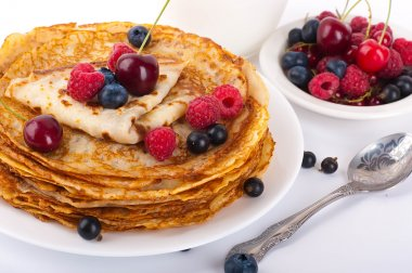 Pancakes with berries on a white background