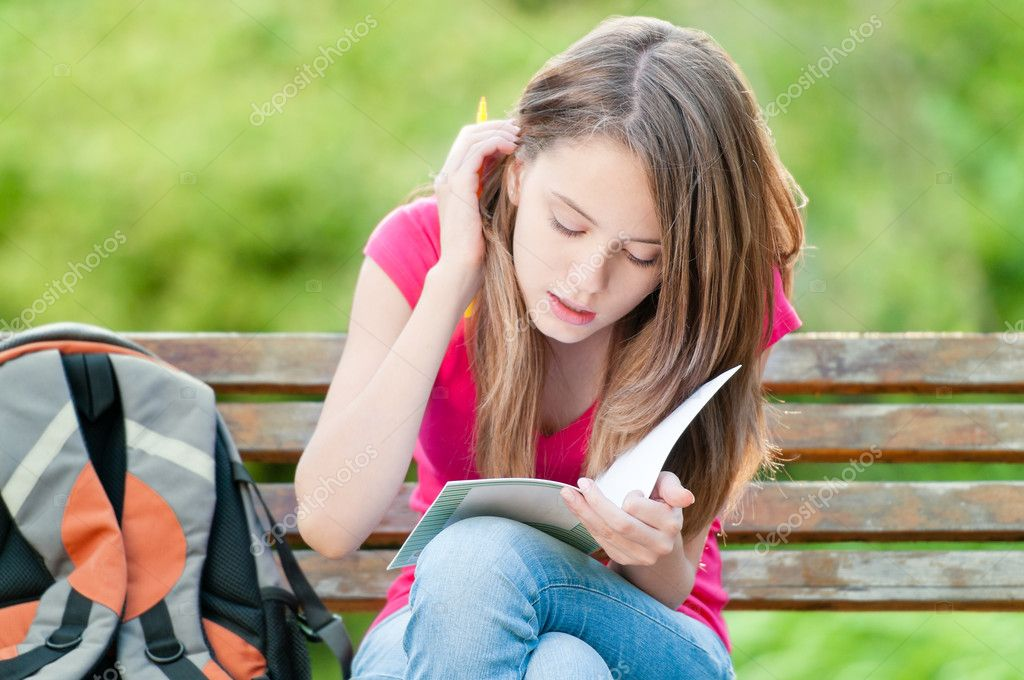 Young student girl sitting on bench