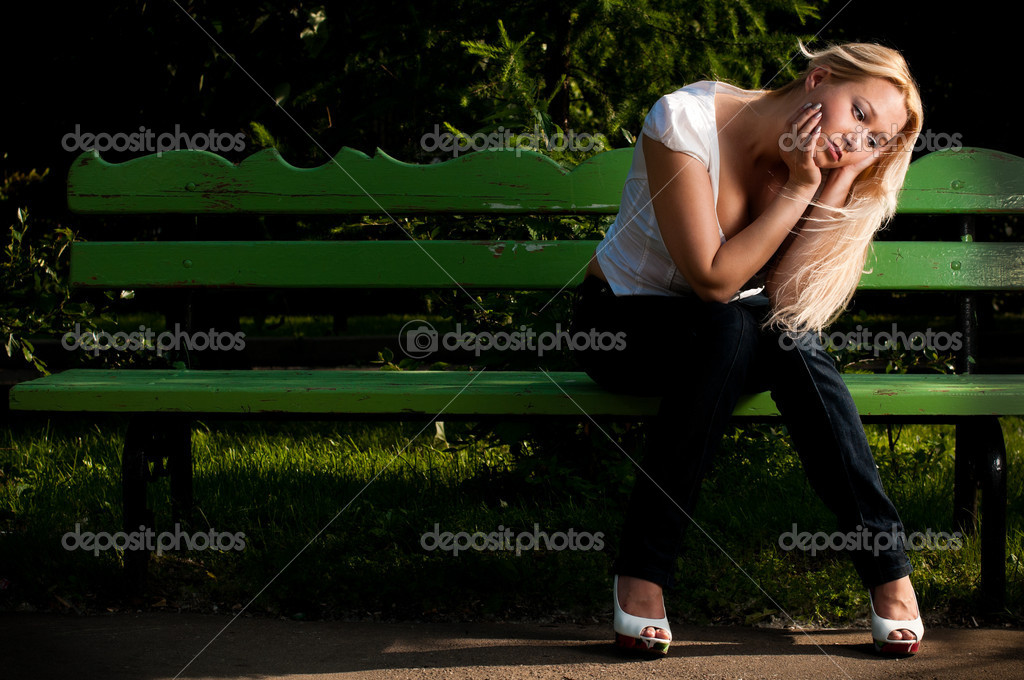 Sad young woman sitting on bench in park