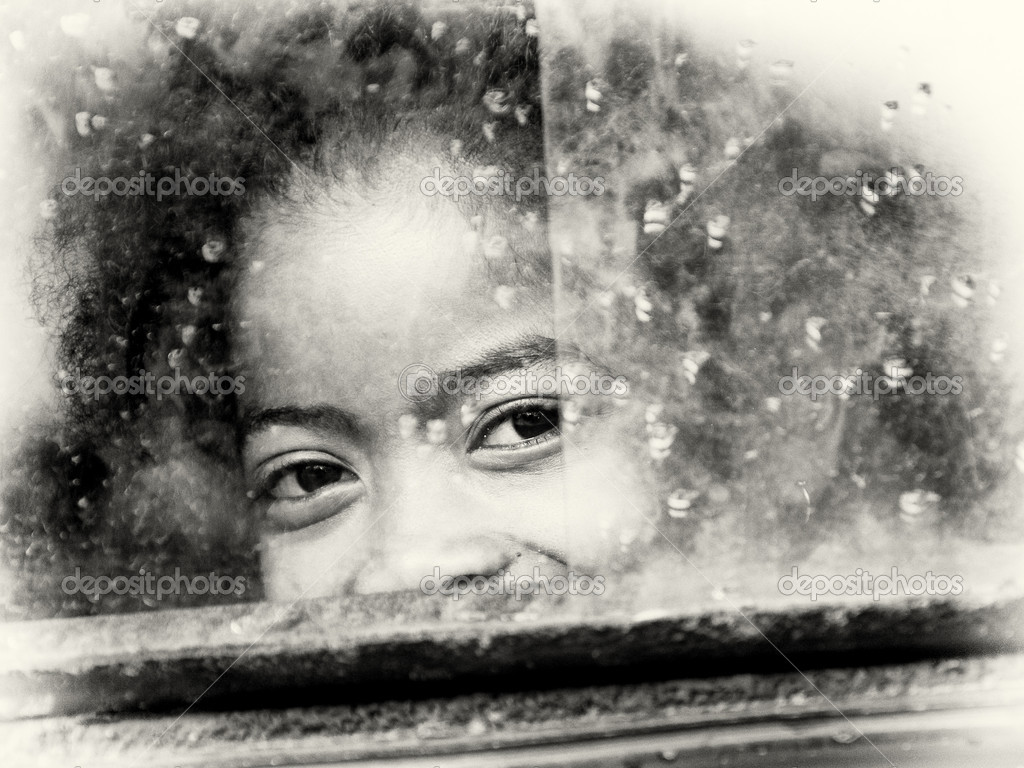 Little girl from Madagascar smiles behind the window