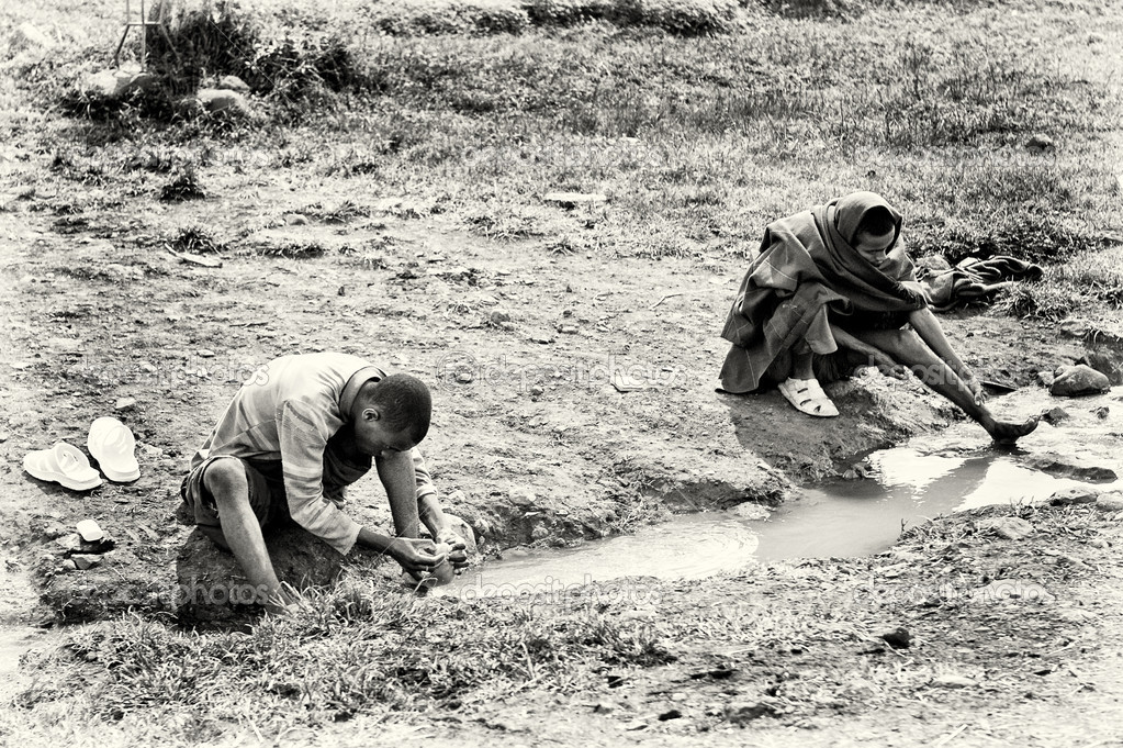 Two Ethiopian men clean their feet in the water