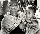 Egy azonosítatlan etióp nő gyermekét tartja a kezét