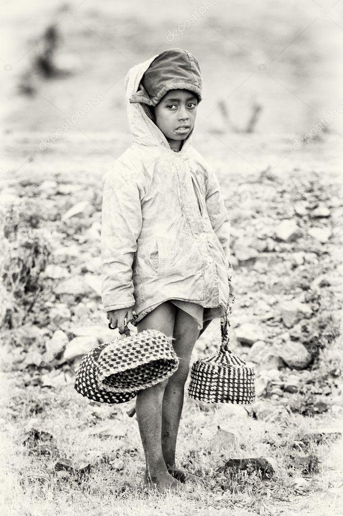 An Ethiopian girl carries hats in her hands