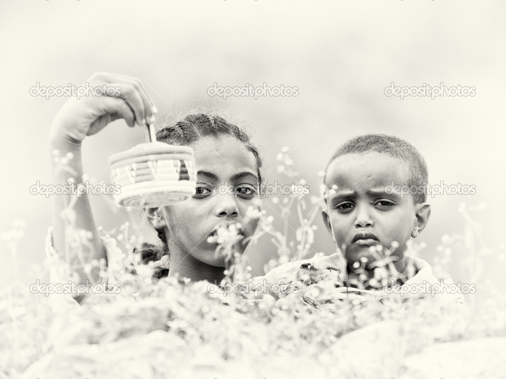 Ethiopian boy and girl sell birds in the cage