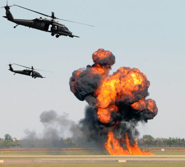 Helicopters mounting a ground attack with explosions and smoke stock vector