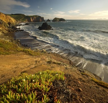 Sunset over Pacific Ocean and steep cliffs in California