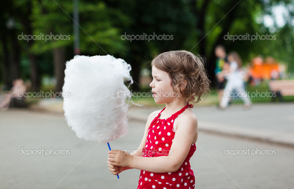 Beautiful little girl eating cotton candy in the park