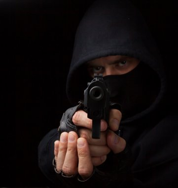 Masked robber with gun aiming into the camera against a black background stock vector