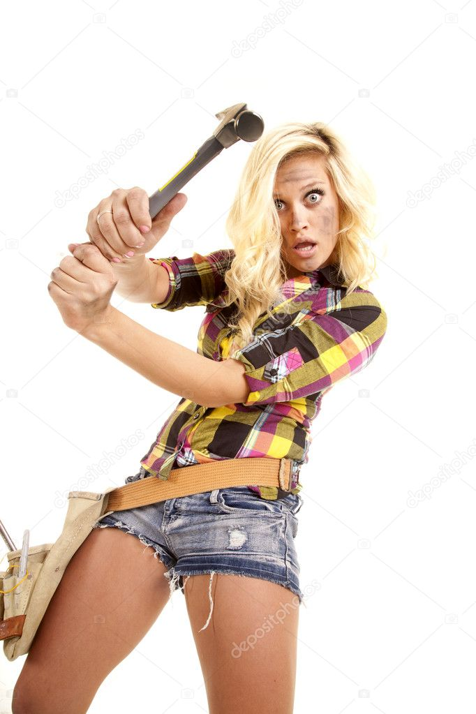 Woman swinging hammer looking