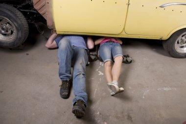 Man woman working on car legs