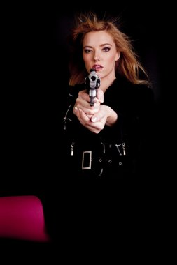 Woman pointing gun pink hair blowing