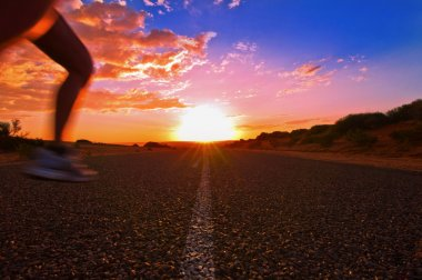 Woman is running while Sun is rising above a endless road in the Australian Outback, Monkey Mia, Western Australia, Australia