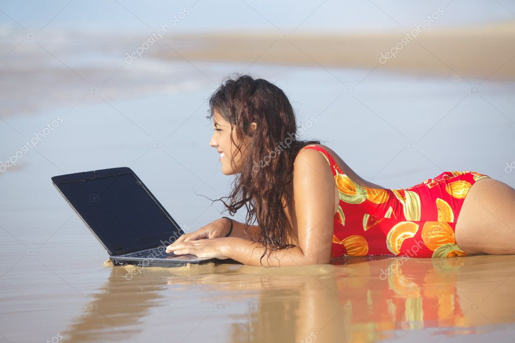 Woman using laptop on beach
