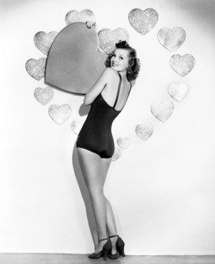 Portrait of woman holding large valentine